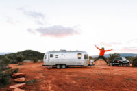 A man jumping in front of his Airstream while traveling in Sedona