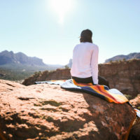 A person sitting on a rock looking at the view of Sedona